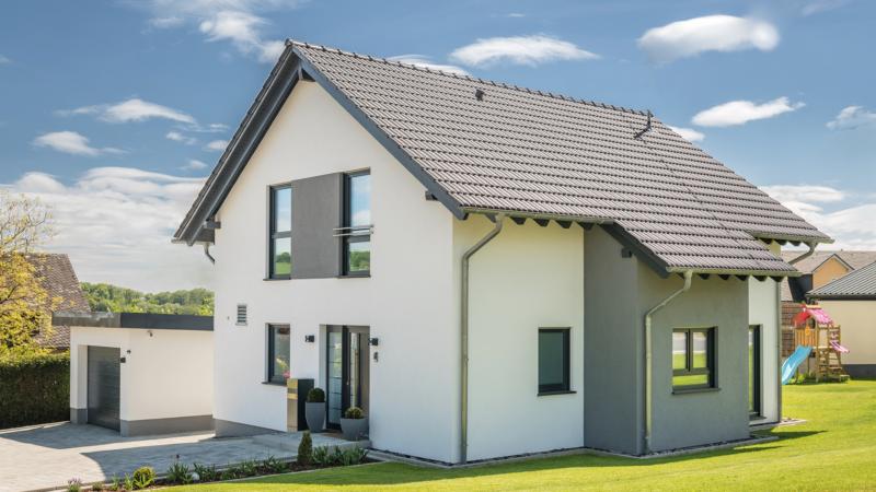 Familie baut mit Fingerhut Haus auf Wohngesundheit im modernen Satteldachhaus